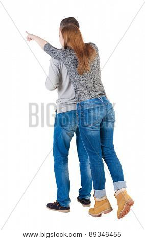young couple pointing at wal Back view  (woman and man). Rear view people collection. She stood on tiptoes shows something in front of a hand.