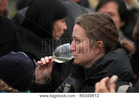 PRAGUE, CZECH REPUBLIC - NOVEMBER 11, 2012: Woman tastes young wine during the celebration of Saint Martin Day in Prague, Czech Republic.