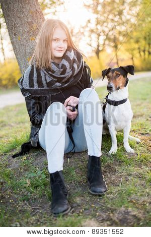 Cute Teenager girl with her Dog in beautiful park.