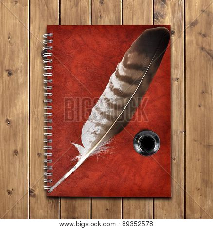Notebook and feather with ink bottle