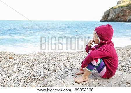 Girl Relaxing On A Pebbly Beach
