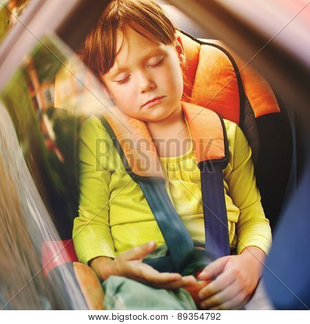 a small girl sleeps in car