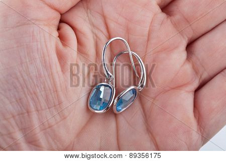 Pair of sapphire earrings in the palm of a female hand