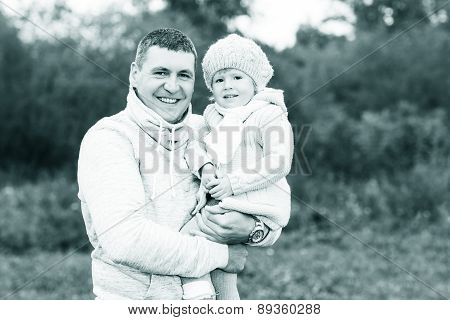 Happy young father holding his little daughter