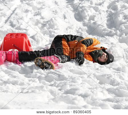 Young Boy Falls From Red Sleigh In The Mountains