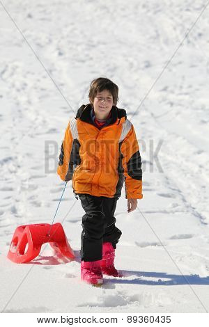 Boy Having Fun On The Red Sleigh In The Mountains In Winter