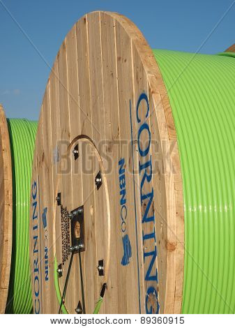 Large timber drums with green fiber optic cable in a transport hub for freight,