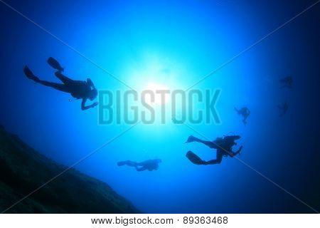 Scuba divers silhouette against sun