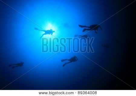 Scuba divers silhouette against sun