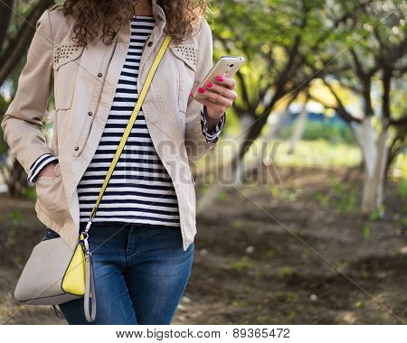 Girl Uses A Telephone In A Beige Jacket And Blue Jeans