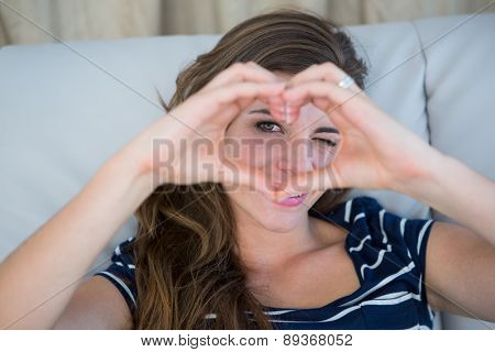 Smiling brunette making heart with her hands in the sofa