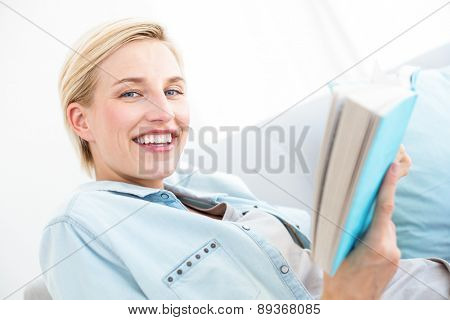 Pretty blonde woman reading a book on the couch in the living room
