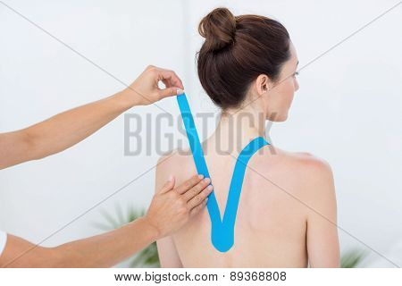Physiotherapist applying blue kinesio tape to patients back in medical office