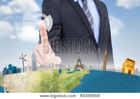 Mid section of businessman pointing something up against blue sky