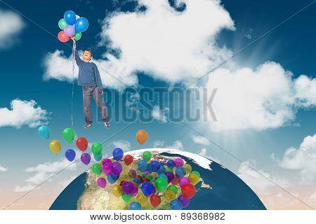 Cute boy holding balloons against blue sky