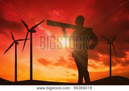 Handyman holding wood planks against sky and mountains