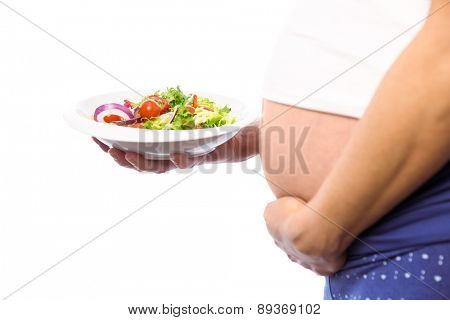 Pregnant woman eating a salad on white background