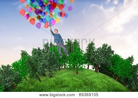 Cute boy holding balloons against beautiful orange and blue sky
