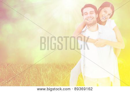 Happy casual man giving pretty girlfriend piggy back against field against glowing lights