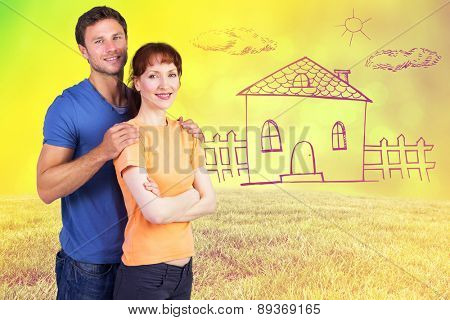 Happy couple looking at camera against field against glowing lights