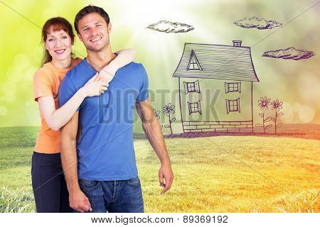 Happy couple looking at camera against field with glowing sky