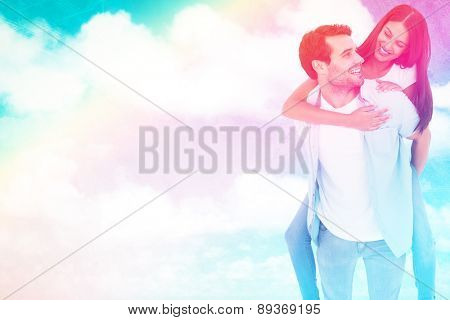 Happy casual man giving pretty girlfriend piggy back against painted sky