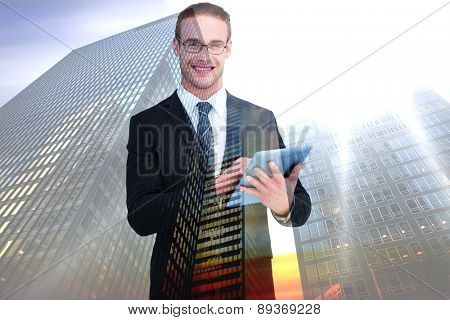 Happy businessman using his tablet pc against low angle view of skyscrapers at sunset