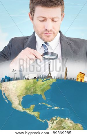 Businessman looking at tablet with magnifying glass against blue sky