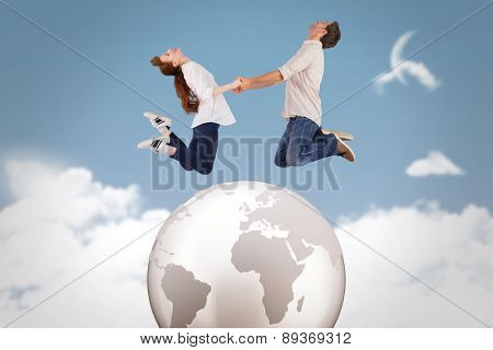 Couple jumping and holding hands against night sky