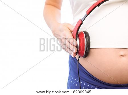 Pregnant woman holding earphones over bump on white background