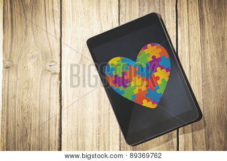 Autism awareness heart against overhead of tablet on desk