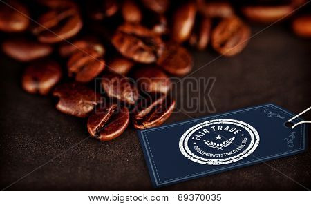 Fair Trade graphic against dark blurred coffee seeds laid out together on a black table