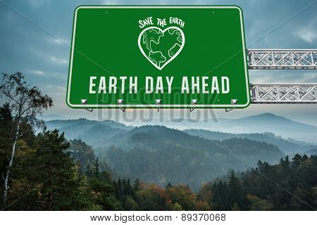 earth day ahead against trees and mountain range against cloudy sky