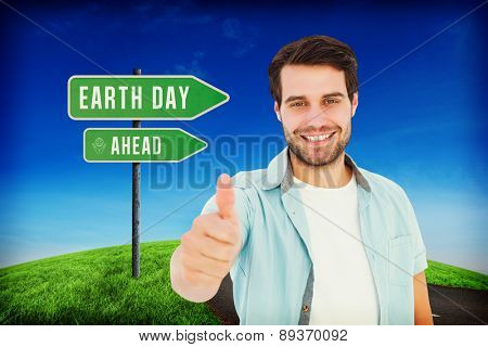 Happy casual man showing thumbs up against road leading out to the horizon
