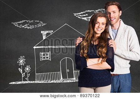 Portrait of smiling young couple against black wall