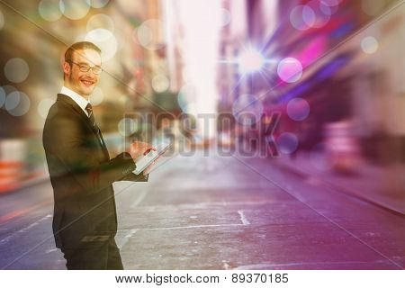 Happy businessman using his tablet pc against blurry new york street