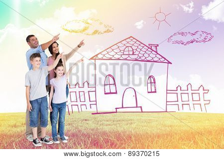 Family of four pointing at copy space against blue sky over green field