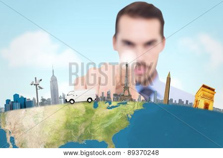 Businessman pointing his finger at camera against blue sky