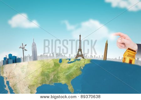 Hand of businessman in suit pointing against blue sky