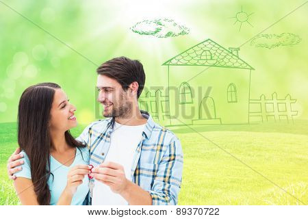 Happy young couple holding new house key against field with glowing sky