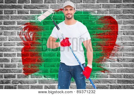 Handyman holding paint roller against red brick wall