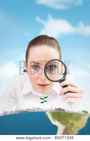 Businesswoman typing and looking through magnifying glass against blue sky