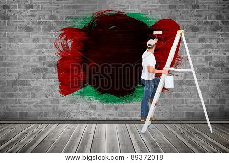 Handyman climbing ladder while using paint roller against grey room