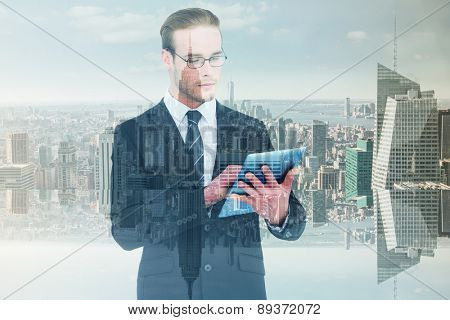Unsmiling businessman using tablet pc against room with large window looking on city