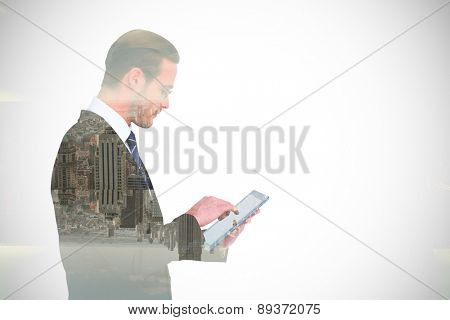 Businessman in reading glasses using his tablet pc against room with large window looking on city