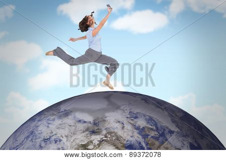 Happy classy businesswoman jumping while holding smartphone against blue sky