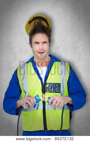 Electrician getting a shock while holding cables against white background