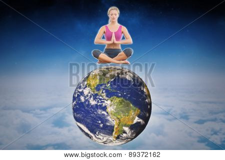 Calm blonde sitting in lotus pose with hands together against white clouds under blue sky