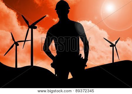 Happy carpenter wearing hard hat against sky and mountains