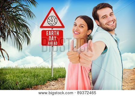 Happy couple showing thumbs up against road leading out to the horizon